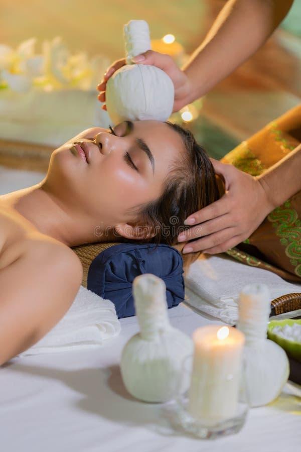 Młoda Azja piękna kobieta podczas masażu z zdroju ziołowym compre obraz stock