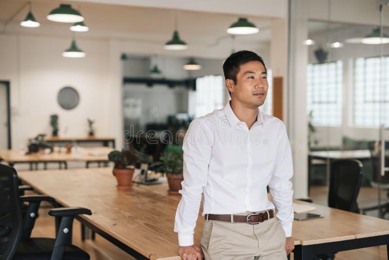 Młoda Azjatycka biznesmen pozycja w biurze głęboko w myśli zdjęcie stock