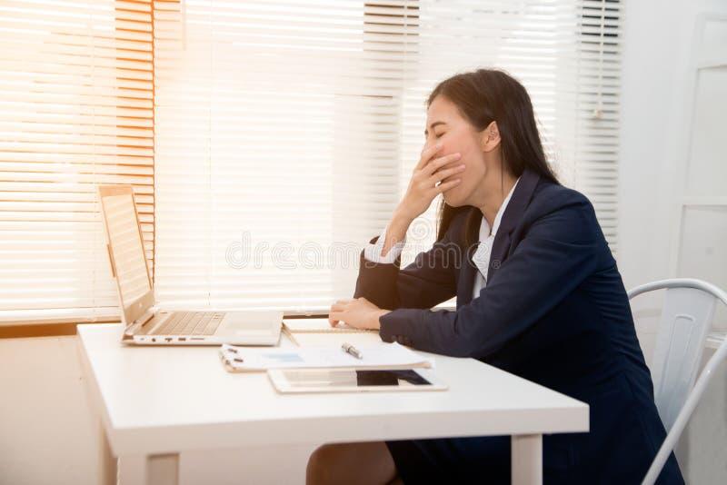 Młoda azjatycka biznesmenka przytulała się do biurka, bo zmęczona przepracowała obrazy royalty free