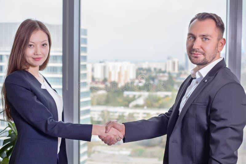 Młoda Azjatycka biznesowa kobieta w kostiumu trząść ręki z jego partnerem biznesowym zdjęcia stock