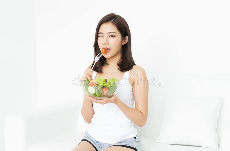 M?oda Azjatycka kobieta jest odpoczynkowa i jedz?ca zdrowego sa?atkowego mruganie zdjęcia royalty free