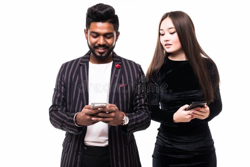 Młoda azjatycka kobieta szpiegująca i podglądająca na smartfon swojego chłopaka z indii na białym tle zdjęcia royalty free