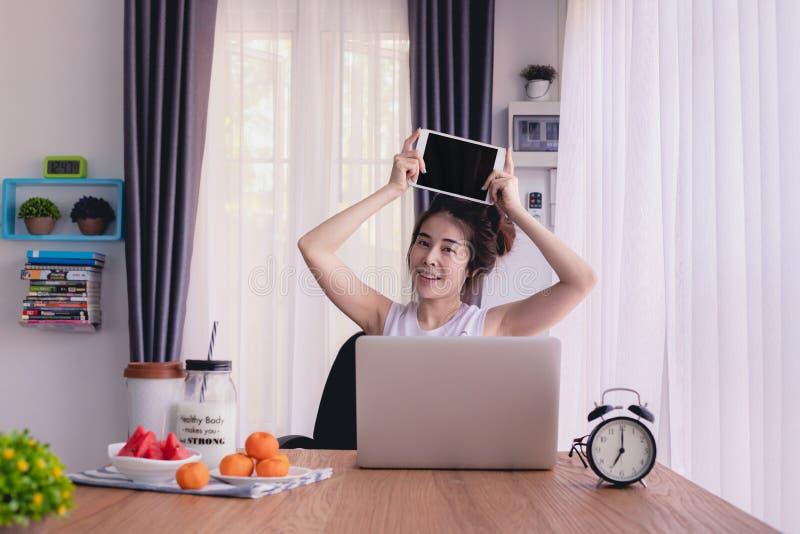Młoda azjatycka kobieta wyświetlająca pusty ekran na laptopie w salonie obrazy stock