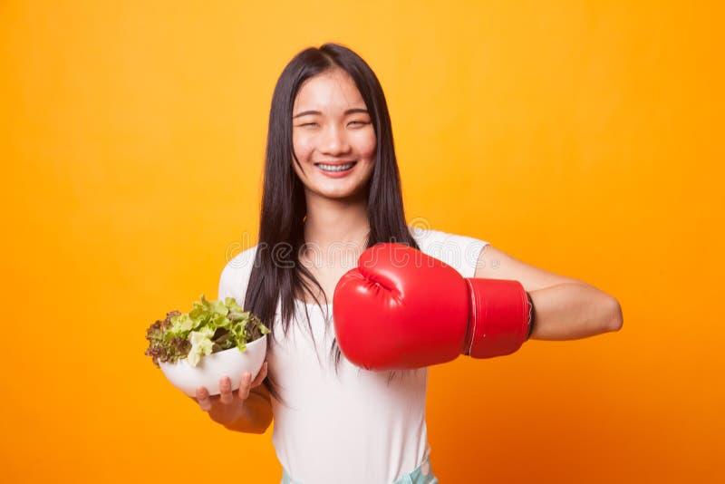 Młoda Azjatycka kobieta z bokserską rękawiczką i sałatką obraz royalty free