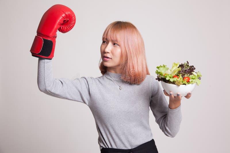 Młoda Azjatycka kobieta z bokserską rękawiczką i sałatką obraz stock