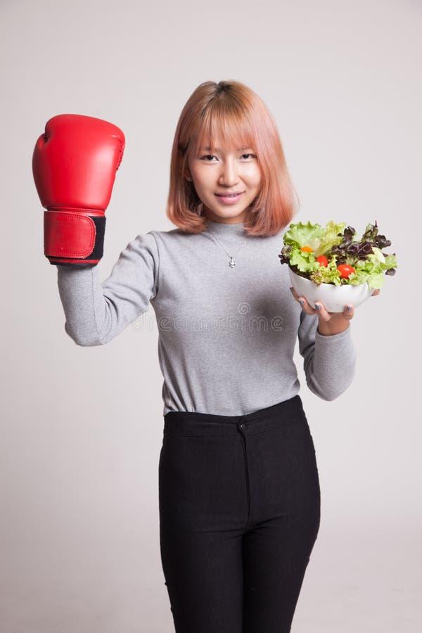 Młoda Azjatycka kobieta z bokserską rękawiczką i sałatką zdjęcia stock