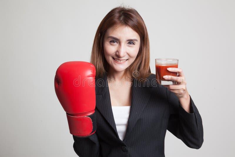 Młoda Azjatycka kobieta z pomidorowym sokiem i bokserską rękawiczką obrazy royalty free