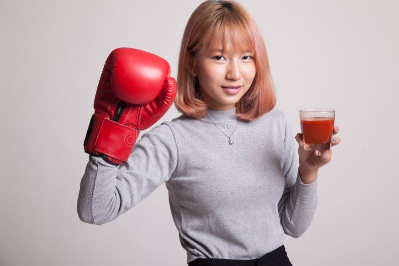 Młoda Azjatycka kobieta z pomidorowym sokiem i bokserską rękawiczką fotografia stock