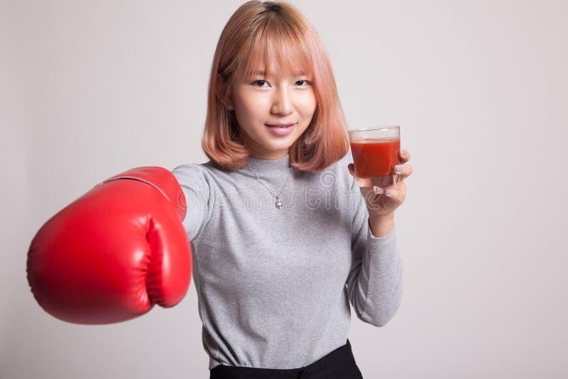 Młoda Azjatycka kobieta z pomidorowym sokiem i bokserską rękawiczką zdjęcie stock