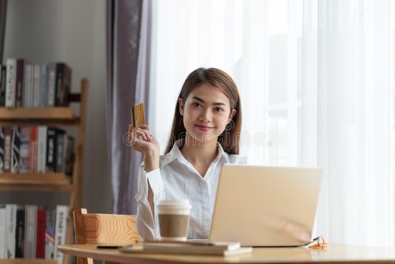 Młoda Azjatycka kobiety mienia karta kredytowa i główkowanie online zakupy w internecie, szczęśliwy i relaksujemy zdjęcie stock