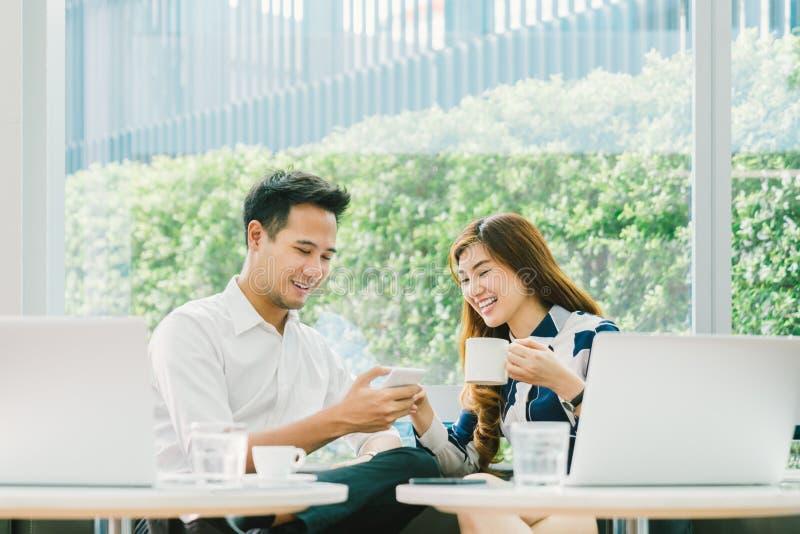 Młoda Azjatycka para, coworkers lub partnery biznesowi, zabawę używać smartphone wpólnie, z laptopem przy sklep z kawą obrazy royalty free