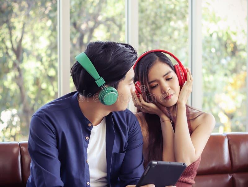Młoda azjatycka para nosząca słuchawki siedząca blisko siebie na kanapie w salonie, kobieta lubi słuchać muzyki, mężczyzna fotografia royalty free