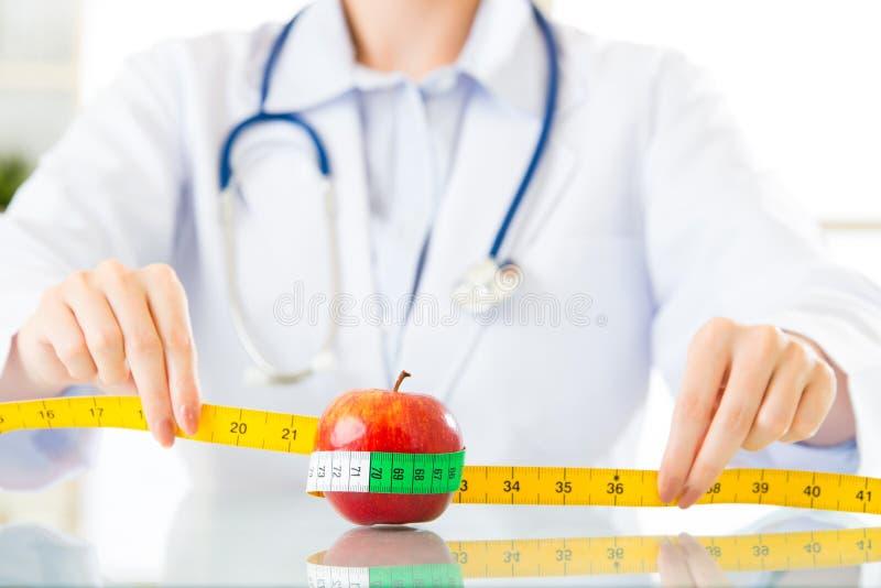 Młoda azjatykcia żywiona lekarka mierzy jabłka obraz stock