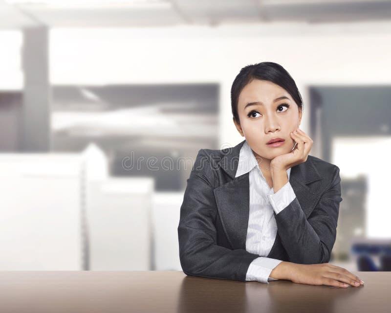 Młoda azjatykcia biznesowa kobieta pracuje przy biurowym biurkiem i myślącym s obrazy stock