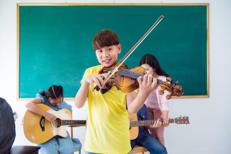 Młoda azjatykcia chłopiec ono uśmiecha się podczas gdy bawić się skrzypce w muzycznej klasie przy s obraz royalty free