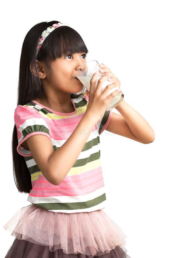 Młoda azjatykcia dziewczyna pije mleko fotografia royalty free