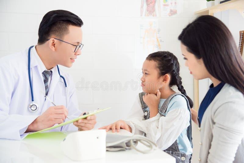 Młoda azjatykcia dziewczyna z bolesnym gardłem przychodzącym wizyty lekarka z ona fotografia stock