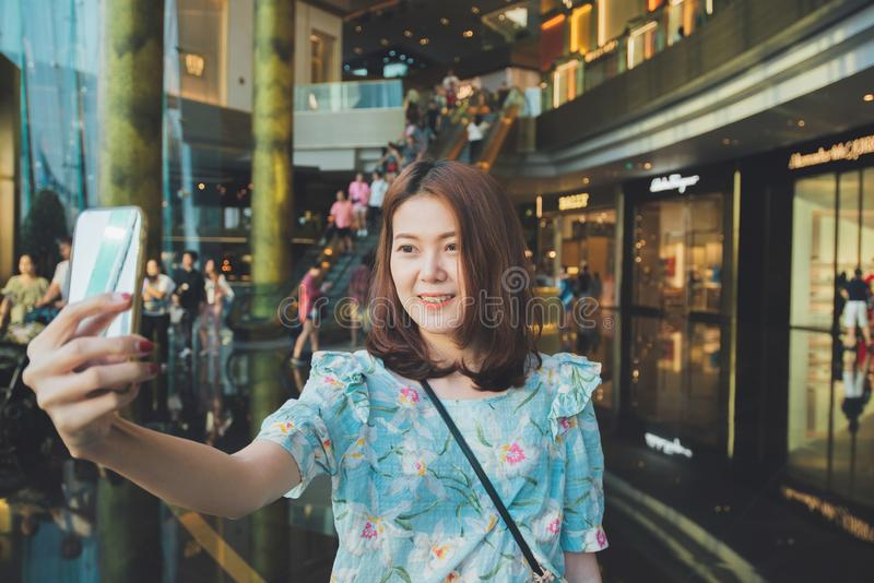 Młoda azjatykcia kobieta bierze selfie podczas gdy robiący zakupy obraz stock
