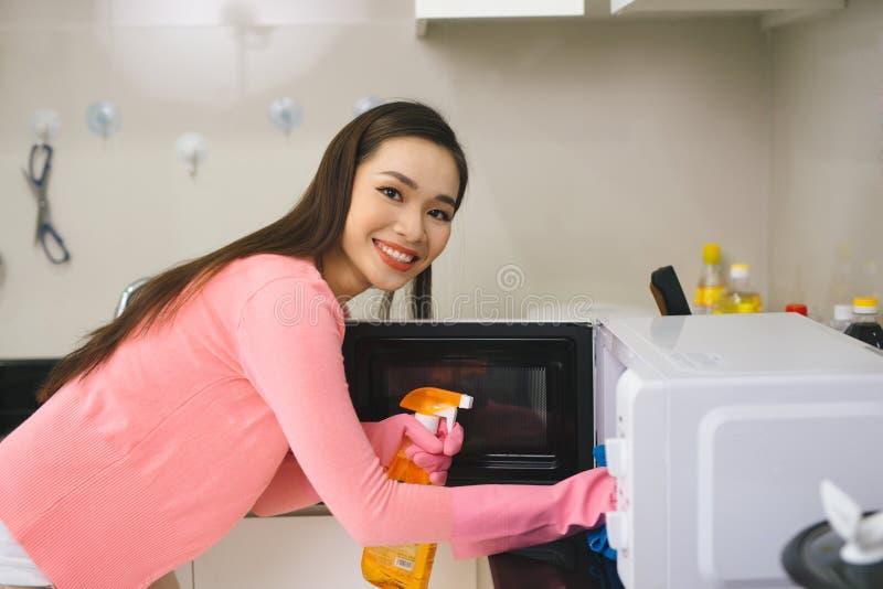 Młoda azjatykcia kobieta czyści kuchnię z detergentową kiścią fotografia royalty free