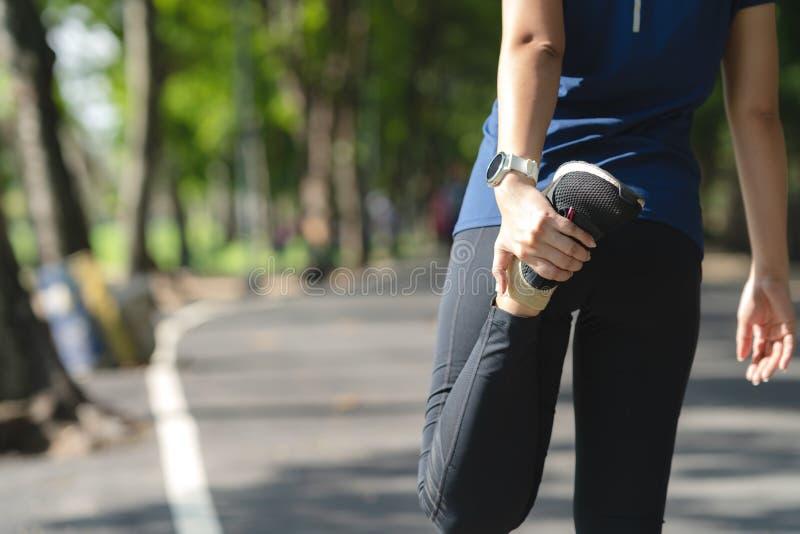 Młoda azjatykcia kobieta grże w górę w dół po biegać w natury miasta jawnym parku zanim trening lub chłodno Cardio sport dla cięż zdjęcie stock
