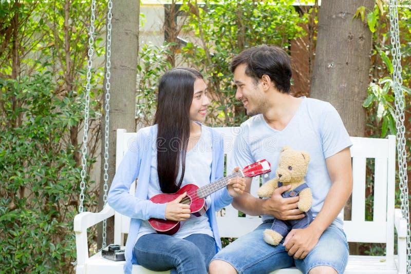 Młoda azjatykcia kobieta i mężczyzna dobieramy się obsiadanie przy parkowym bawić się ukulele i śpiewamy piosenkę outdoors fotografia royalty free