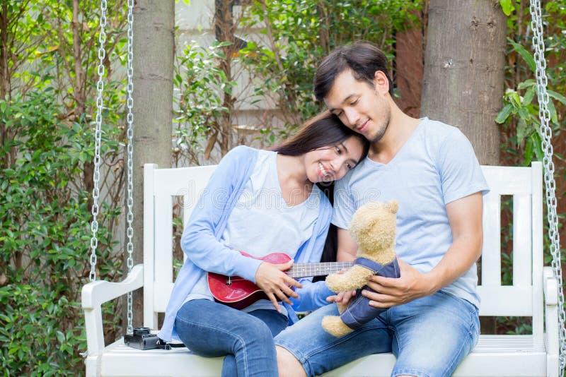 Młoda azjatykcia kobieta i mężczyzna dobieramy się obsiadanie przy parkowym bawić się ukulele i śpiewamy piosenkę outdoors zdjęcia stock