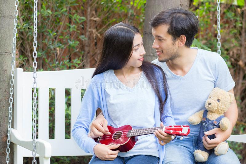 Młoda azjatykcia kobieta i mężczyzna dobieramy się obsiadanie przy parkowym bawić się ukulele obrazy royalty free