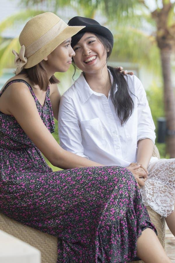Młoda azjatykcia kobieta i uroczy przyjaciel uśmiecha się opowiadać fotografia royalty free