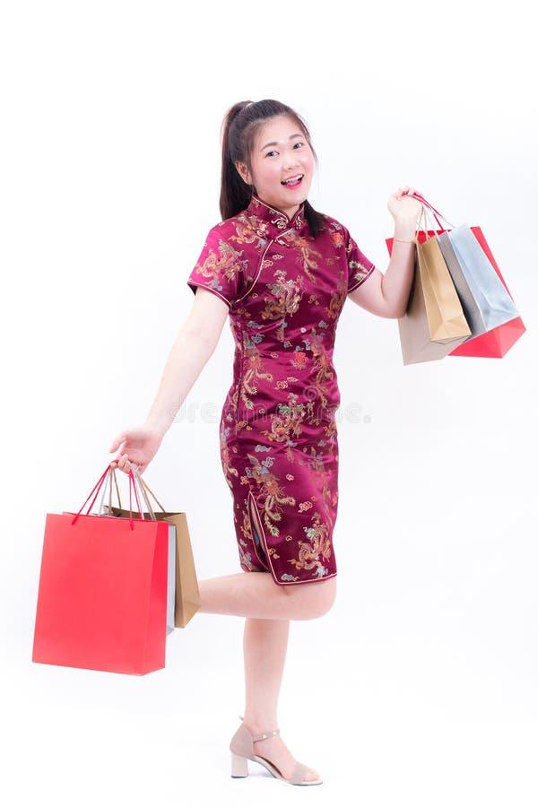 Młoda azjatykcia kobieta jest ubranym chińczyka smokingowego tradycyjnego cheongsam z Nieść uśmiech i torba na zakupy obraz royalty free