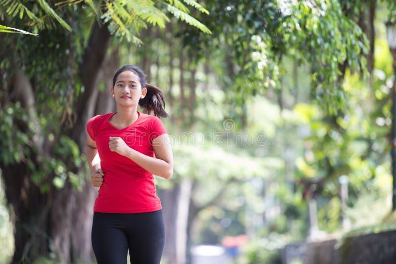 Młoda azjatykcia kobieta jogging przy parkiem fotografia stock