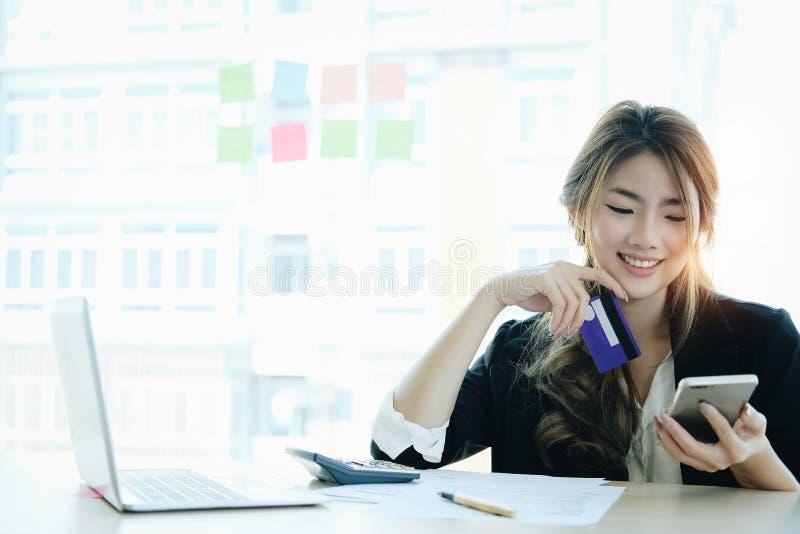 Młoda azjatykcia kobieta płaci z kredytową kartą na mądrze telefonie w domu zdjęcie stock