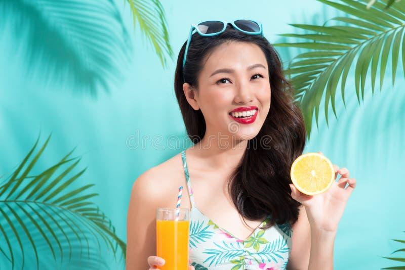Młoda azjatykcia kobieta pije sok od szkła nad kolorowymi błękitnymi półdupkami obrazy stock