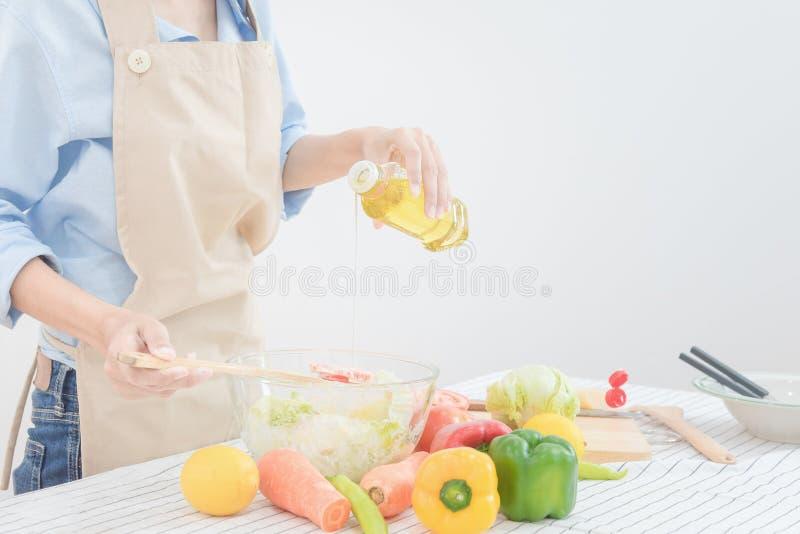 Młoda azjatykcia kobieta przygotowywa zdrowej karmowej sałatki w domu zdjęcia royalty free