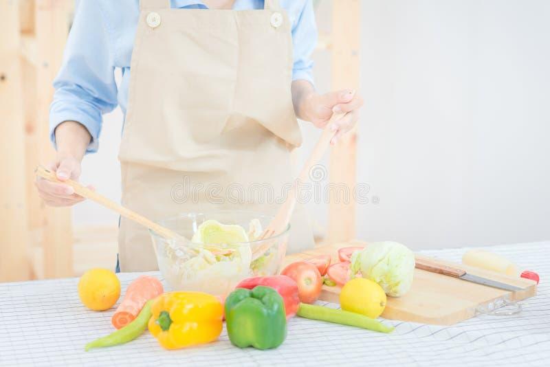 Młoda azjatykcia kobieta przygotowywa zdrowej karmowej sałatki w domu obrazy royalty free
