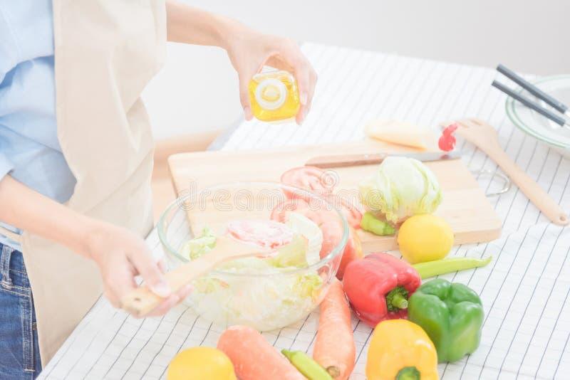 Młoda azjatykcia kobieta przygotowywa zdrowej karmowej sałatki w domu fotografia stock