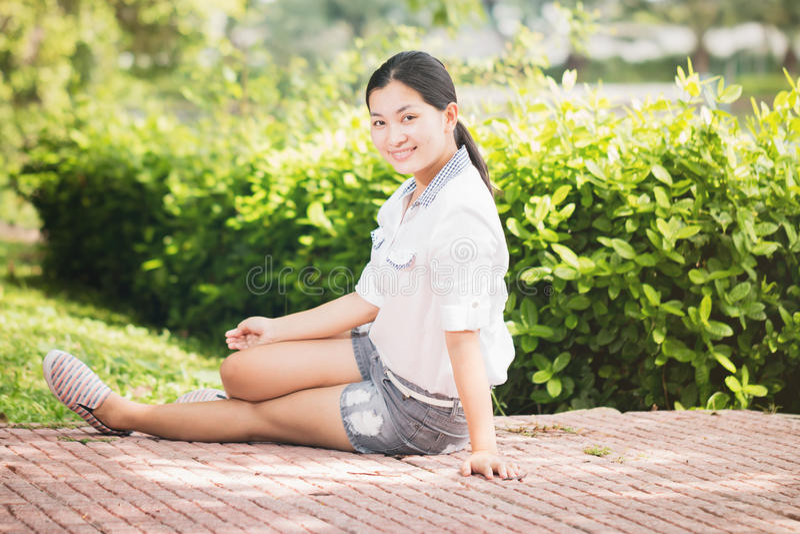 Młoda azjatykcia kobieta relaksuje patrzeć szczęśliwy i uśmiechnięty fotografia stock