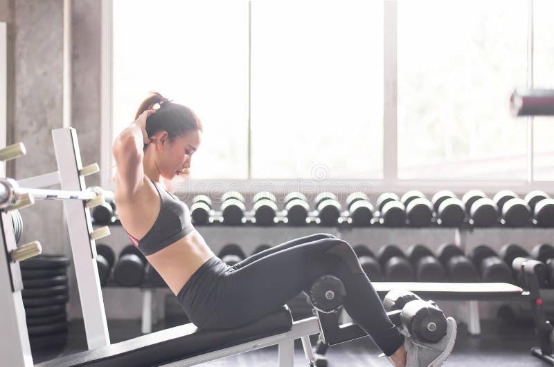 Młoda azjatykcia kobieta robi situp lub chrupnięciom w gym, Żeński ćwiczenie mięśniowy jej żołądek zdjęcia stock