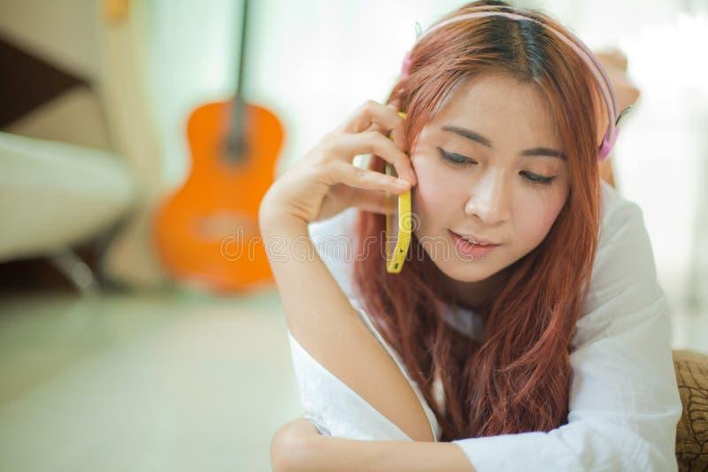 Młoda azjatykcia kobieta słucha muzyka fotografia stock