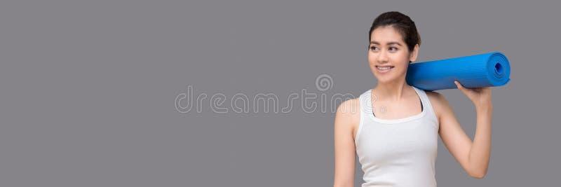Młoda azjatykcia kobieta trzyma jej joga matę i powabny uśmiech podczas gdy iść ćwiczyć joga ćwiczenie przy joga sporta gym zdjęcie royalty free