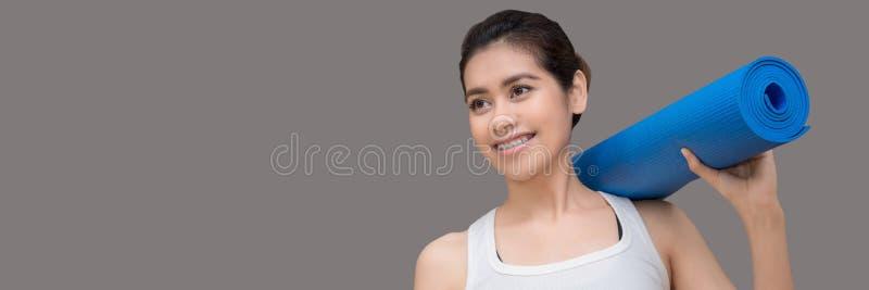 Młoda azjatykcia kobieta trzyma jej joga matę i powabny uśmiech podczas gdy iść ćwiczyć joga ćwiczenie przy joga sporta gym obrazy stock