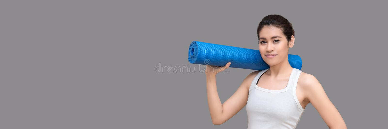 Młoda azjatykcia kobieta trzyma jej joga matę i powabny uśmiech podczas gdy iść ćwiczyć joga ćwiczenie przy joga sporta gym fotografia royalty free