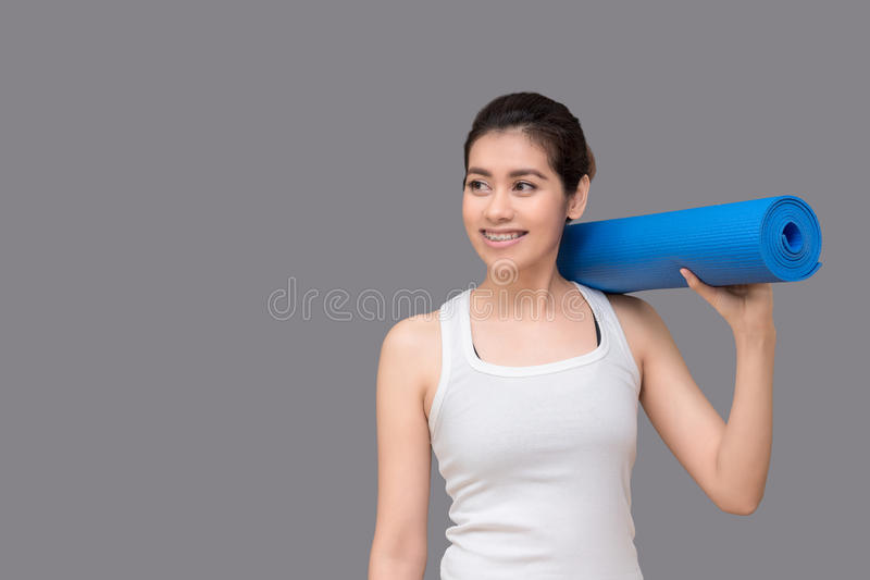 Młoda azjatykcia kobieta trzyma jej joga matę przy zdrowym sporta gym Yog obraz royalty free