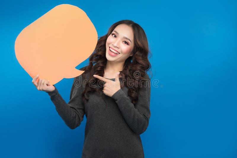 Młoda azjatykcia kobieta trzyma mowa bąbel na błękitnym tle obraz stock