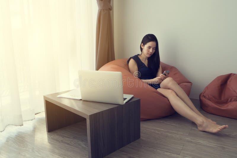 Młoda azjatykcia kobieta używa telefon komórkowego na pomarańczowej bobowej torbie w żywym pokoju obraz royalty free