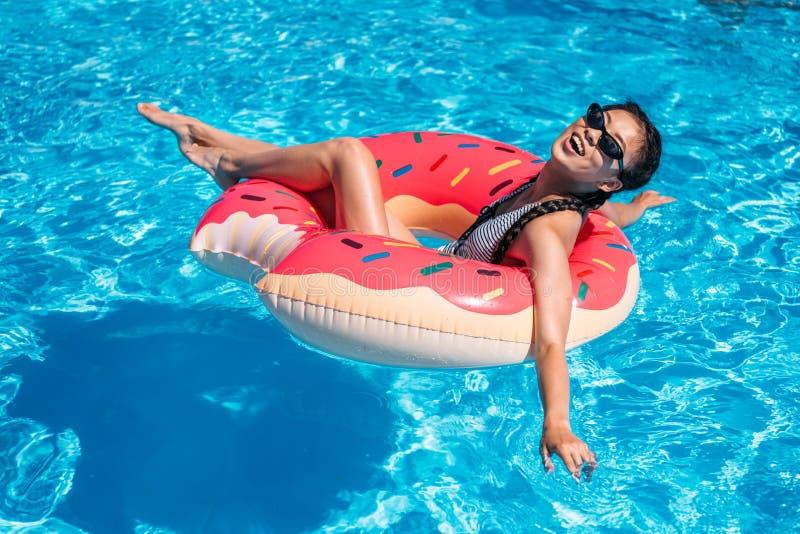 Młoda azjatykcia kobieta unosi się na nadmuchiwanym pączku zdjęcie royalty free