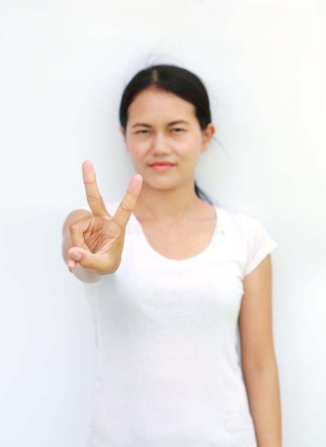 Młoda azjatykcia kobieta w koszulce Pokazuje wyrażeniu palca zwycięstwo, Wybierająca ostrość przy jej palcem zdjęcia royalty free