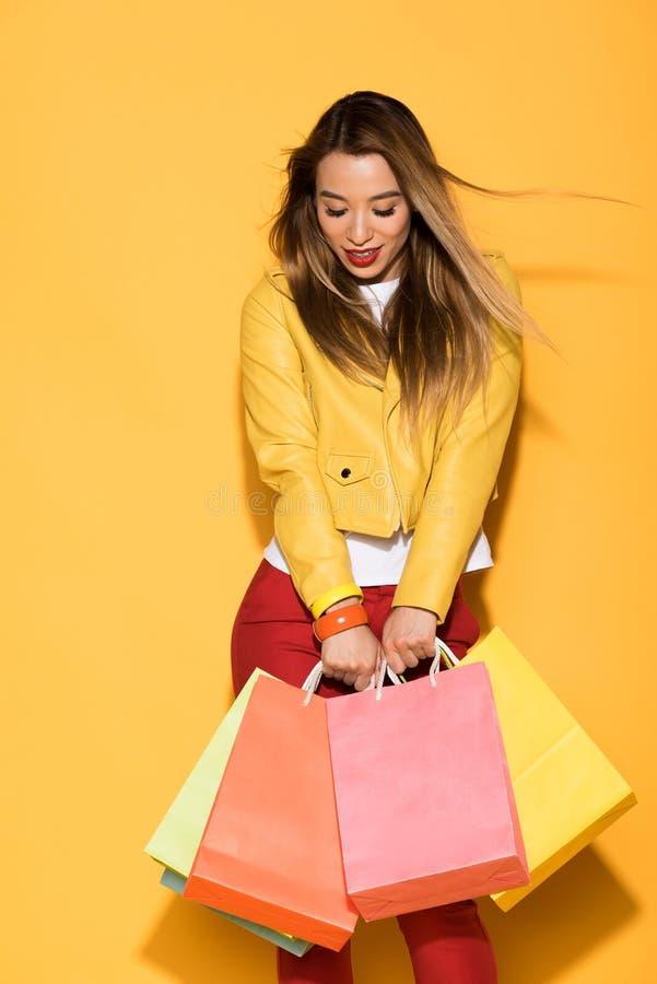 młoda azjatykcia kobieta z torbami na zakupy na kolorze żółtym zdjęcie stock