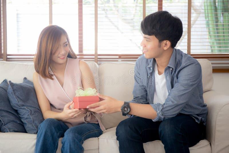 Młoda azjatykcia para świętuje urodziny wpólnie, Asia mężczyzna daje prezenta pudełku teraźniejszemu dla niespodzianki przy żywym fotografia stock