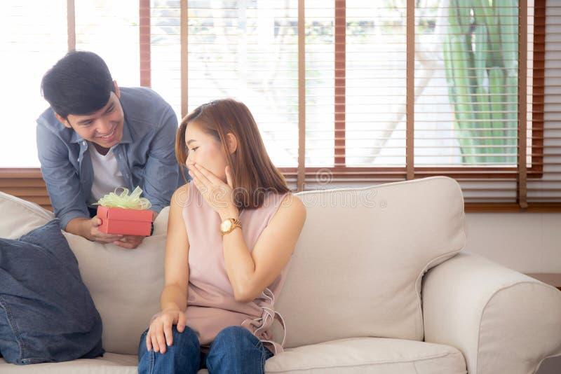 Młoda azjatykcia para świętuje urodziny wpólnie, Asia mężczyzna daje prezenta pudełku teraźniejszemu dla niespodzianki przy żywym zdjęcie royalty free