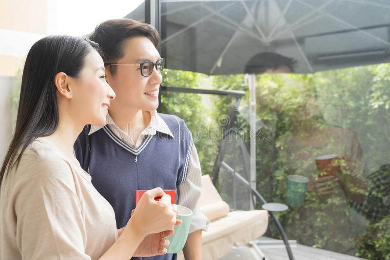 Młoda azjatykcia para indoors patrzeje outside relaksuje z kawą przy nowożytnym domem zdjęcia royalty free